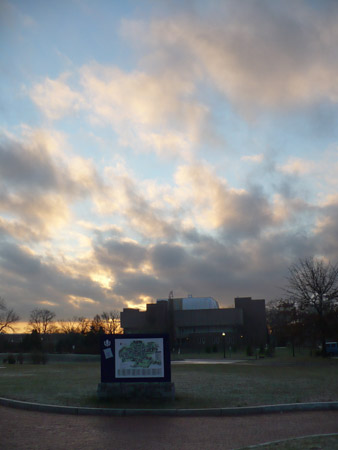 Sunrise over UConn building with campus map